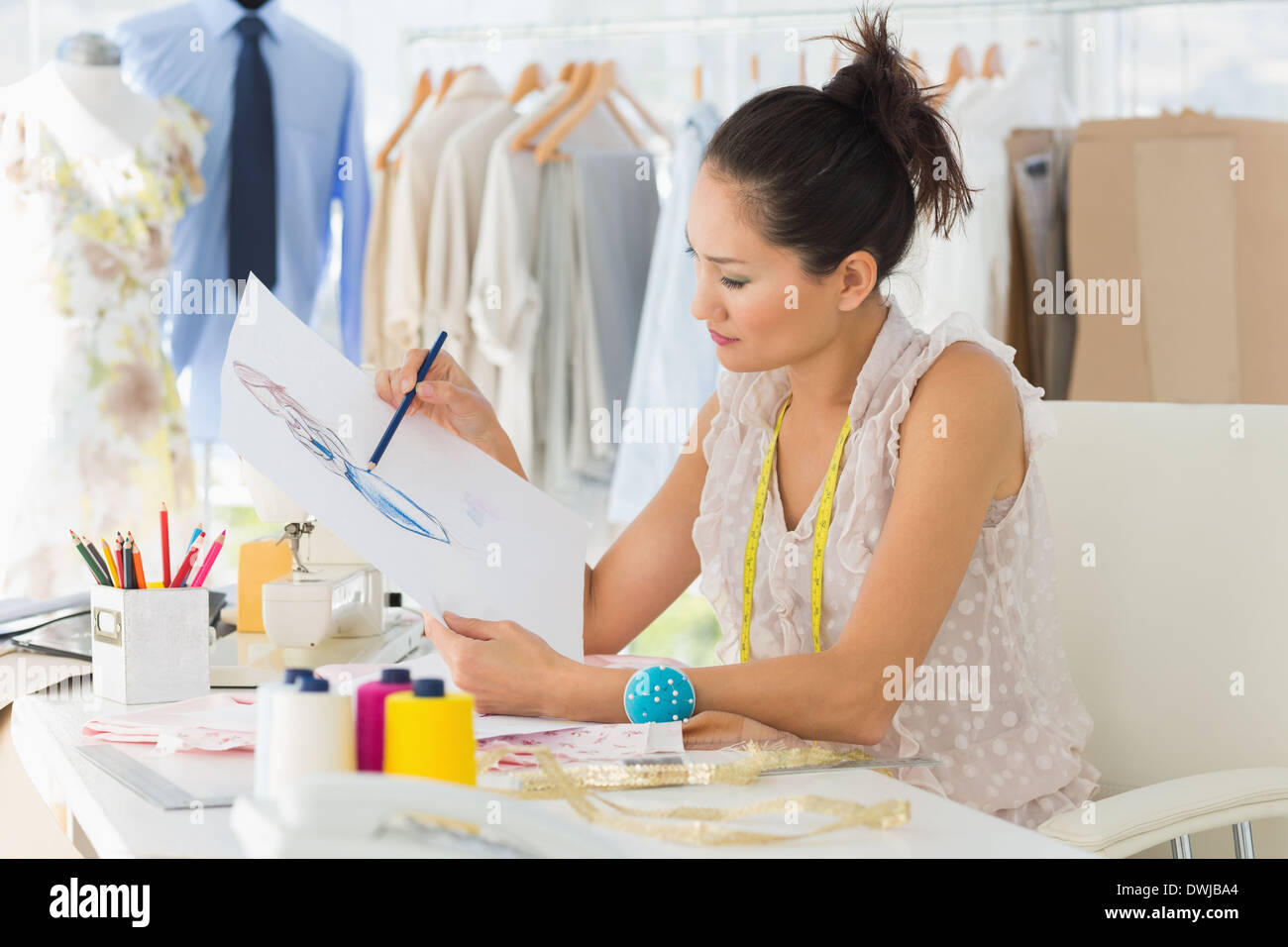 Female fashion designer working on her designs - Stock Image