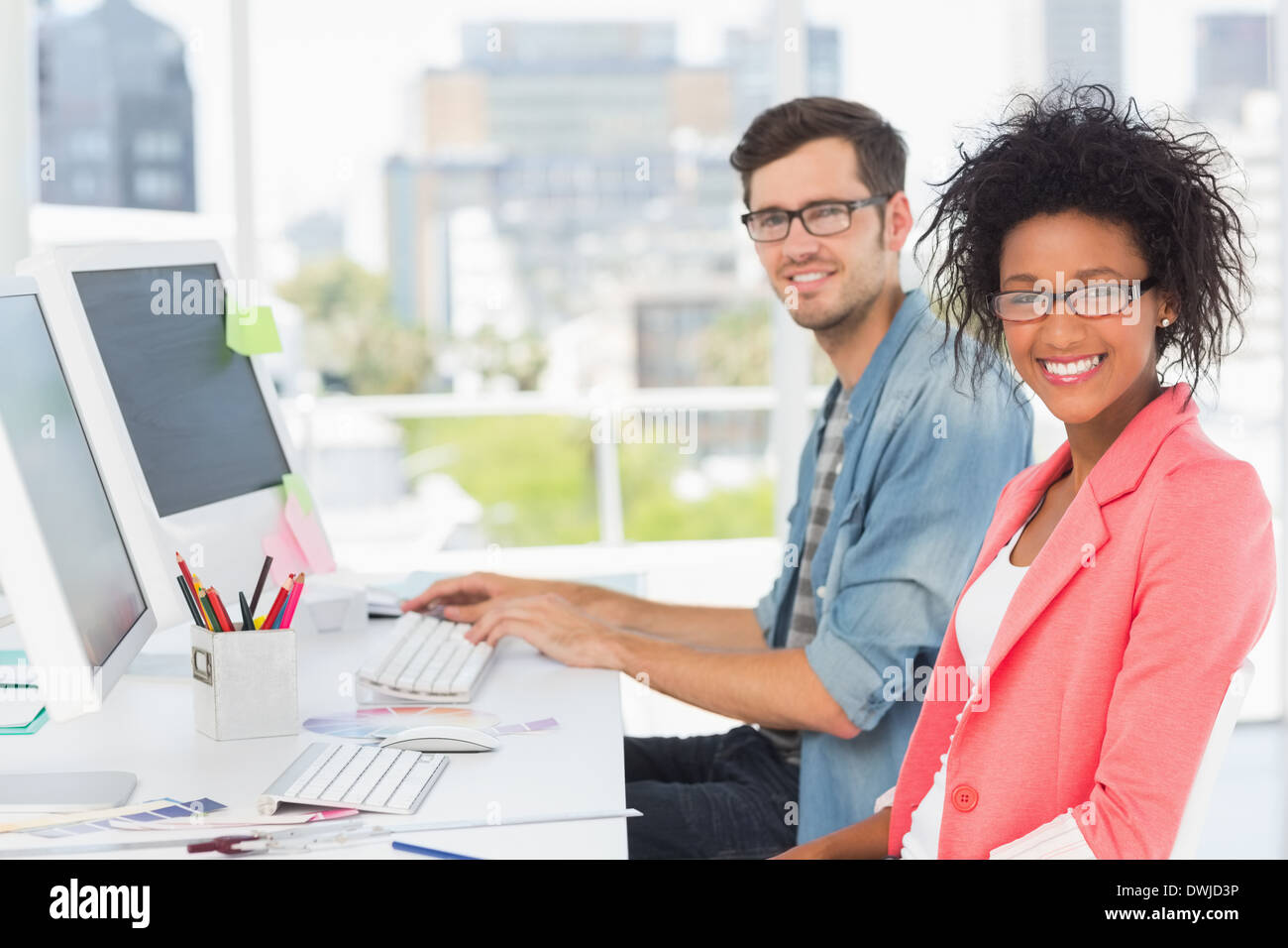 Smiling casual young couple working on computers - Stock Image