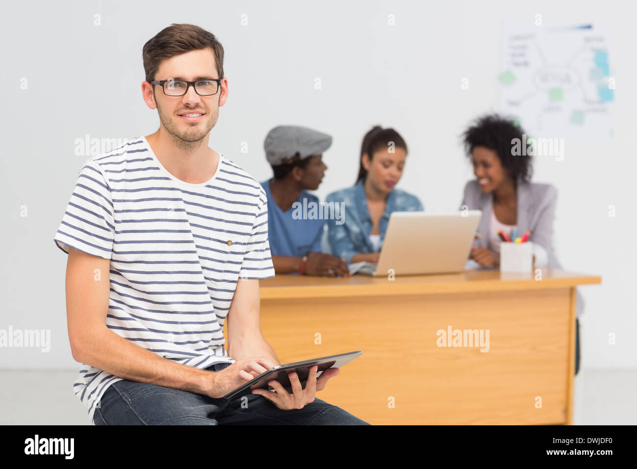 Artist using digital tablet with colleagues in background at office Stock Photo