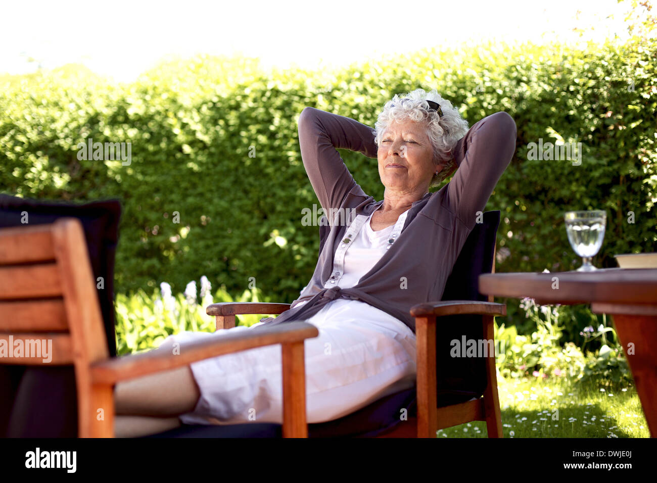 Senior woman sitting on a chair and taking a nap in backyard. Elder woman sleeping in backyard garden - Stock Image