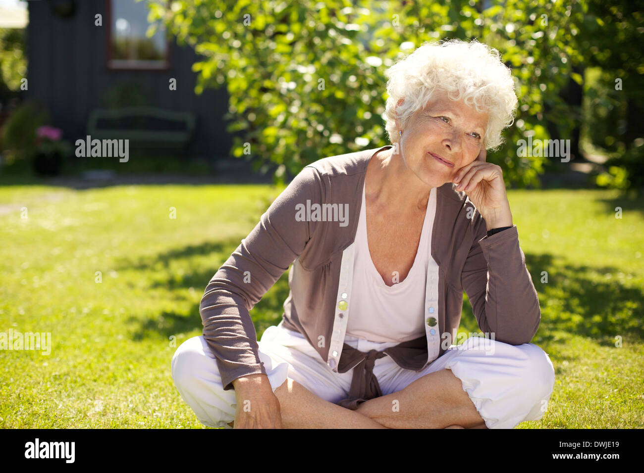Senior woman sitting outdoors on grass looking away and thinking. Elder woman relaxing in backyard garden day dreaming - Stock Image