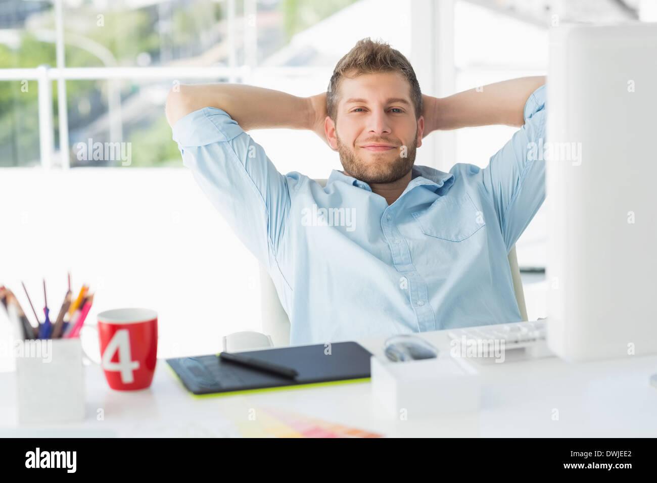 Designer relaxing at his desk smiling at camera - Stock Image