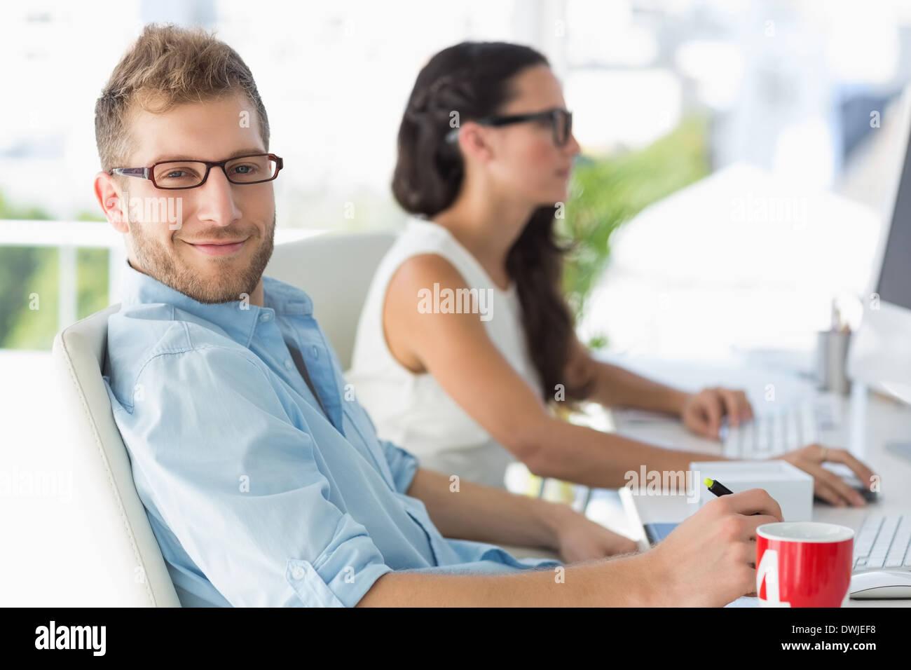 Handsome designer smiling at camera at desk - Stock Image