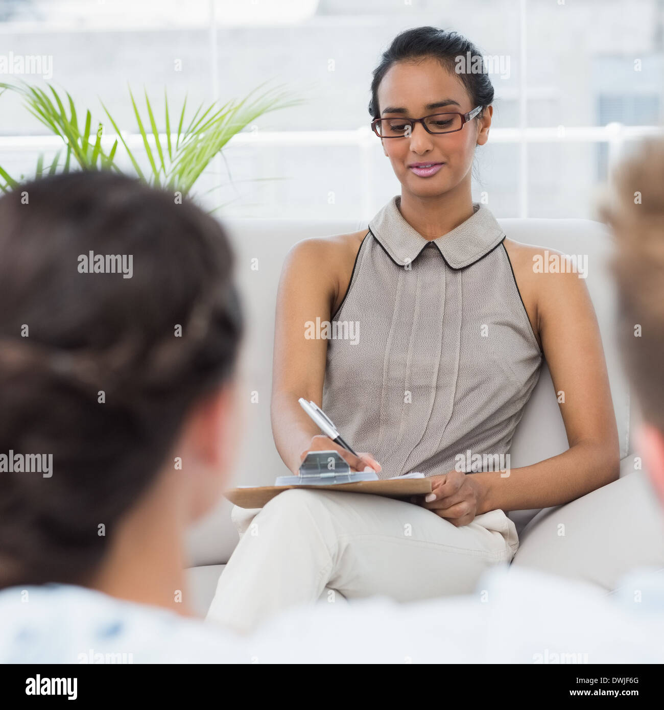 Therapist talking with couple on the couch and taking notes - Stock Image