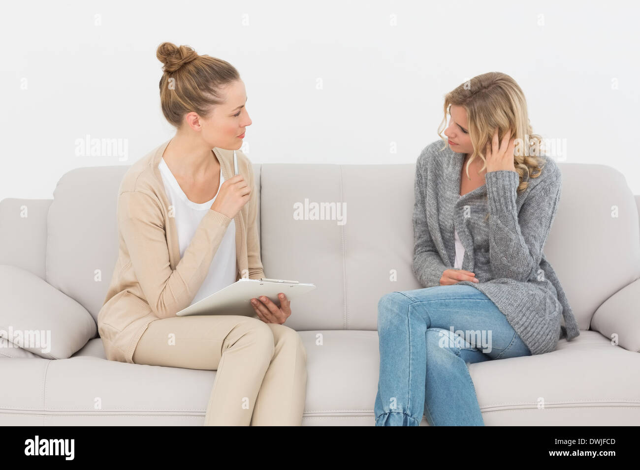 Upset woman talking to her therapist on the couch - Stock Image