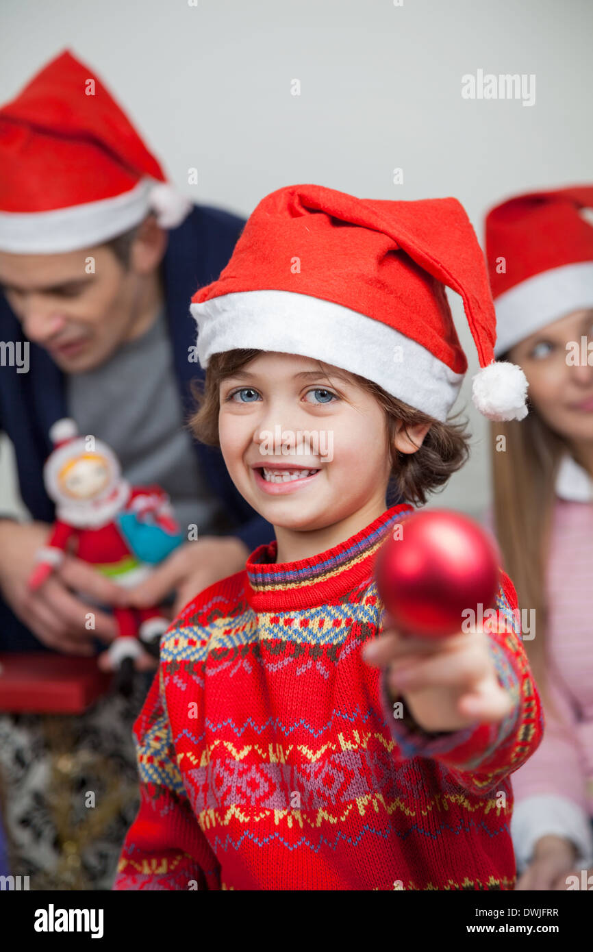 Boy Showing Christmas Decoration At Home - Stock Image