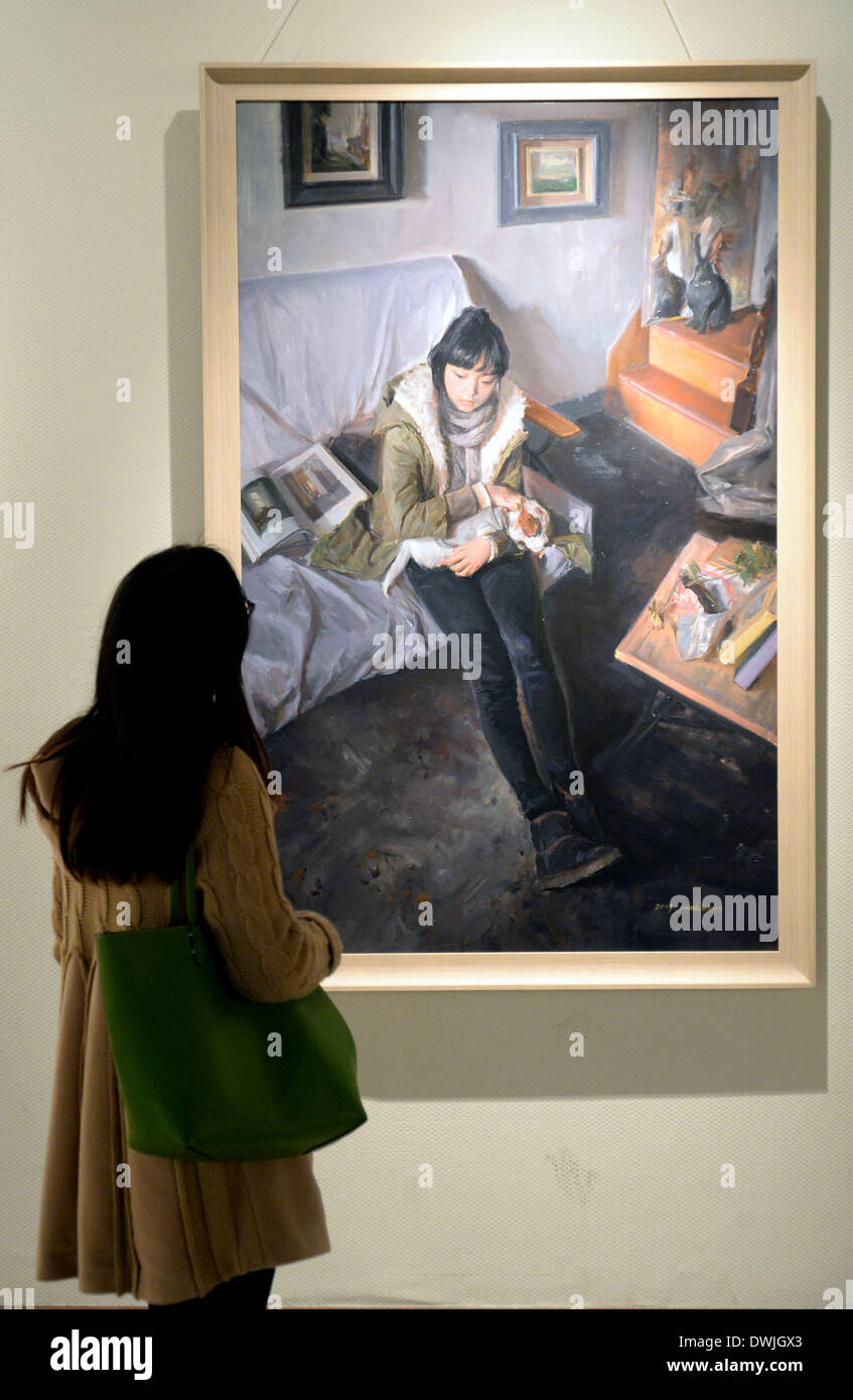 Hangzhou, China's Zhejiang Province. 10th Mar, 2014. A visitor looks at a painting presented during the exhibition 'Babel: Reunite after Bewilderment' in Hangzhou, capital of east China's Zhejiang Province, March 10, 2014. Dozens of artworks by undergraduate students from the China Academy of Art were on display. © Shi Jianxue/Xinhua/Alamy Live News - Stock Image