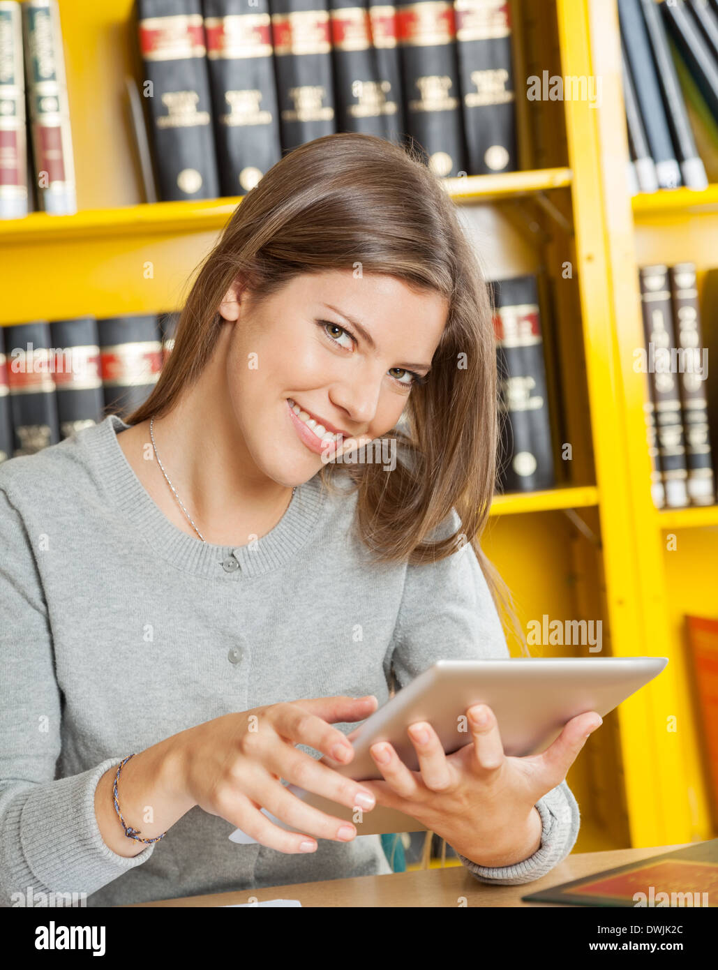 Woman With Digital Tablet Sitting Against Bookshelf In Library - Stock Image