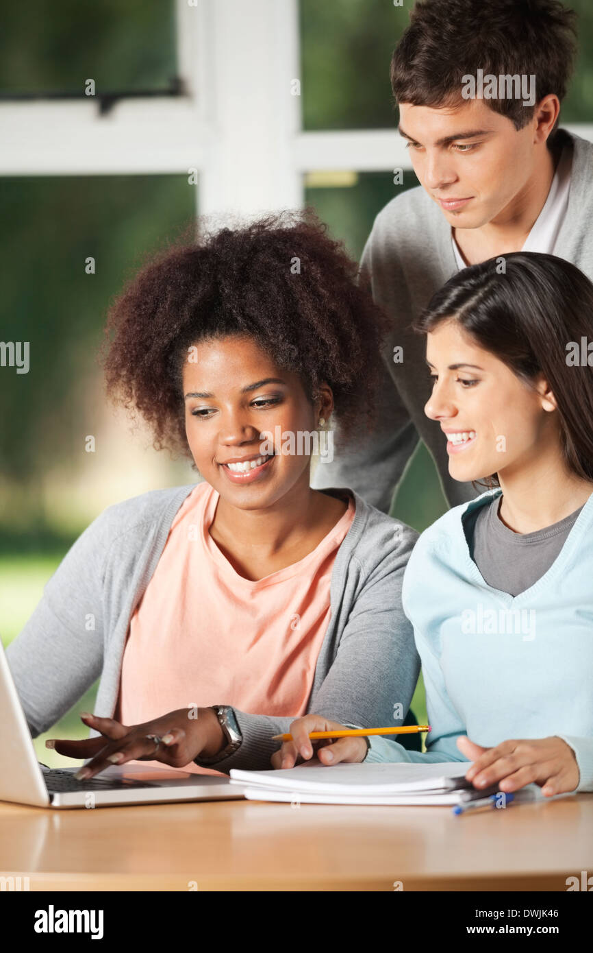 Friends Using Laptop At Desk In Classroom - Stock Image