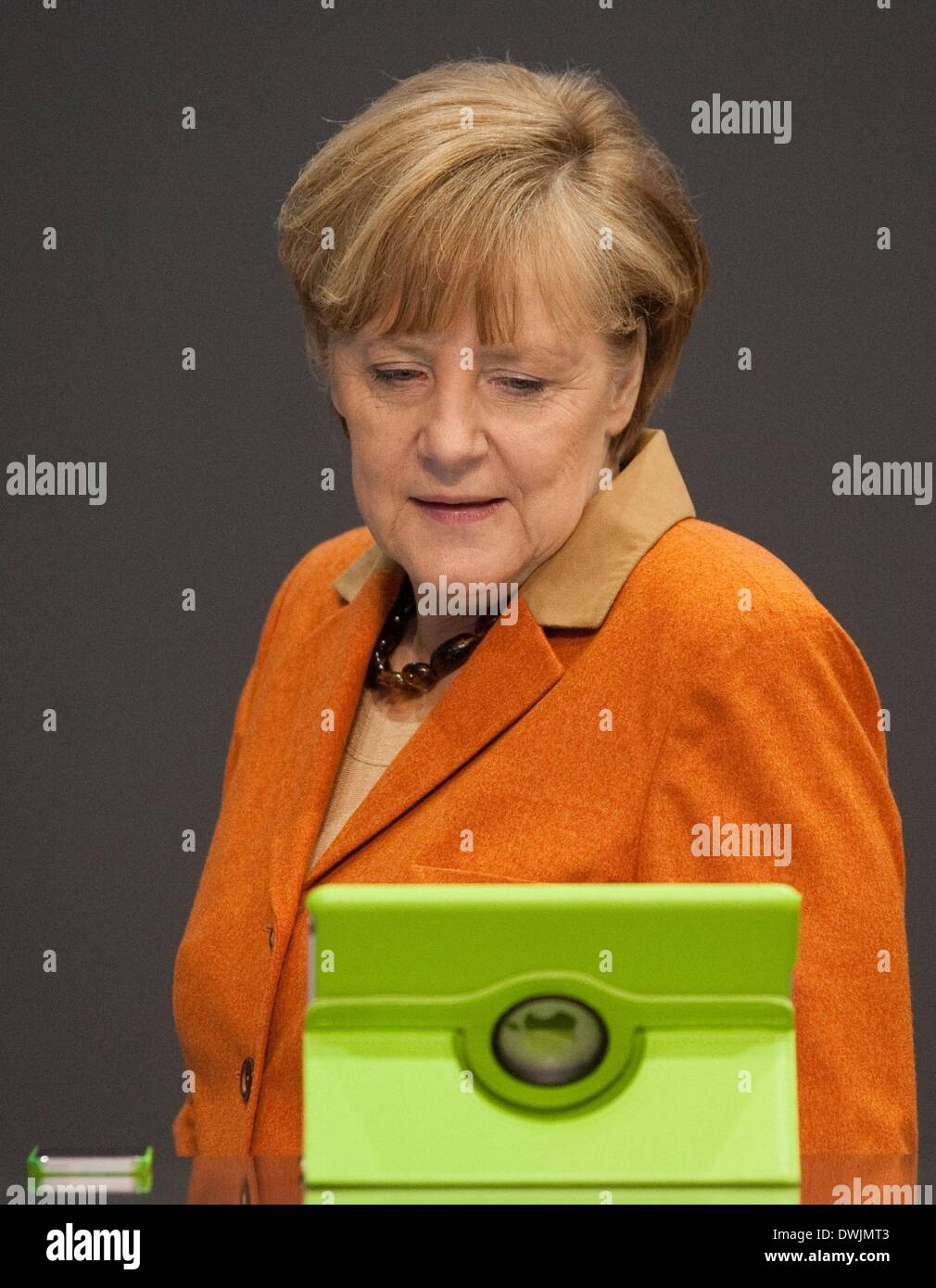 Hanover, Germany. 10th Mar, 2014. German Chancellor Angela Merkel (CDU) looks at an iPad and an iPhone at the booth of the Unify company during her opening tour across the CeBIT fair in Hanover, Germany, 10 March 2014. Great Britian is this year's partner country. The fair runs until 14 March 2014. Photo: Swen Pfoertner/dpa/Alamy Live News - Stock Image