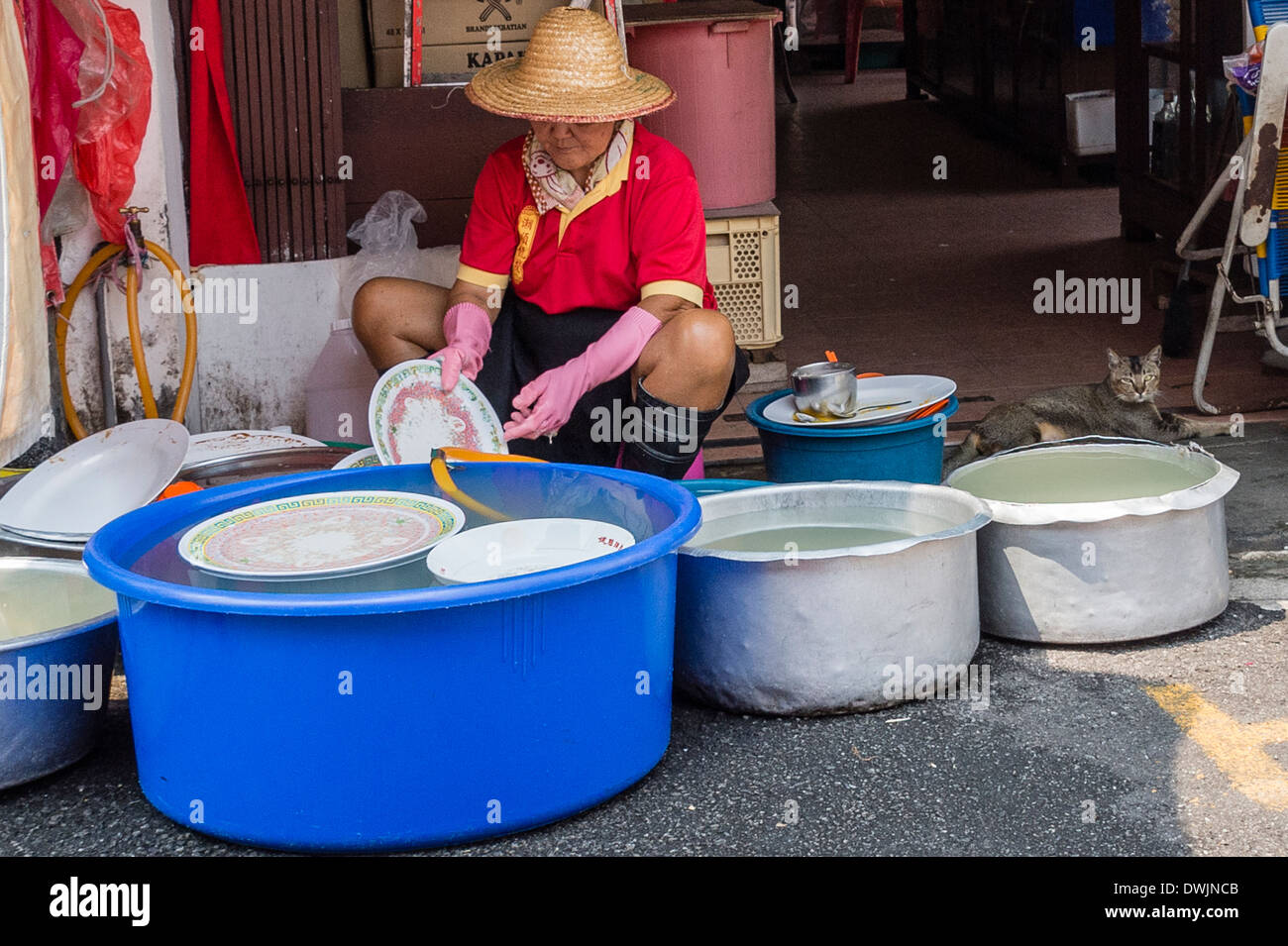 A lady washing dishes in Malacca - Stock Image
