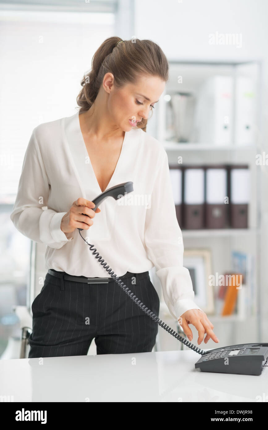 Modern business woman dialing phone - Stock Image