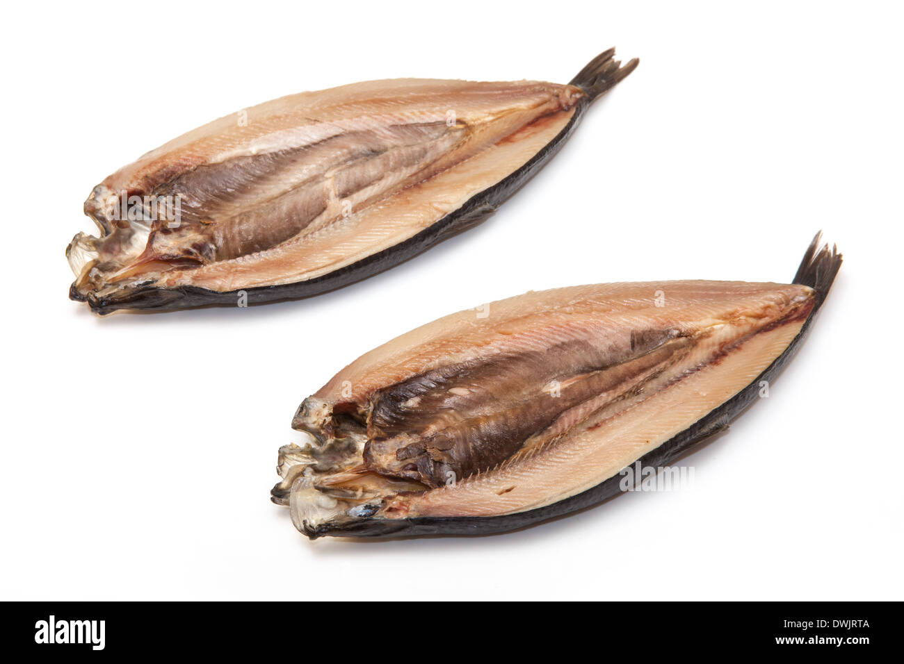 Non-dyed smoked Kippers isolated on a white studio background. - Stock Image