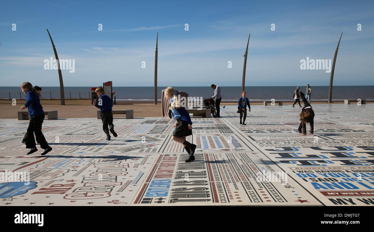 Blackpool, Lancashire, UK. 10th March, 2014. UK Weather. Spring sunshine & High Spirits on the Comedy Pavement enjoyed by children playing, running, chasing on a school trip, and adults on Tower esplanade.  The work of more than 1,000 comedians and comedy writers, the carpet gives visual form to jokes, songs and catchphrases dating from the early days of variety to the present. The 2,200m2 work of art contains over 160,000 granite letters embedded into concrete, pushing the boundaries of public art and typography to their limits. Credit:  Mar Photographics/Alamy Live News. - Stock Image