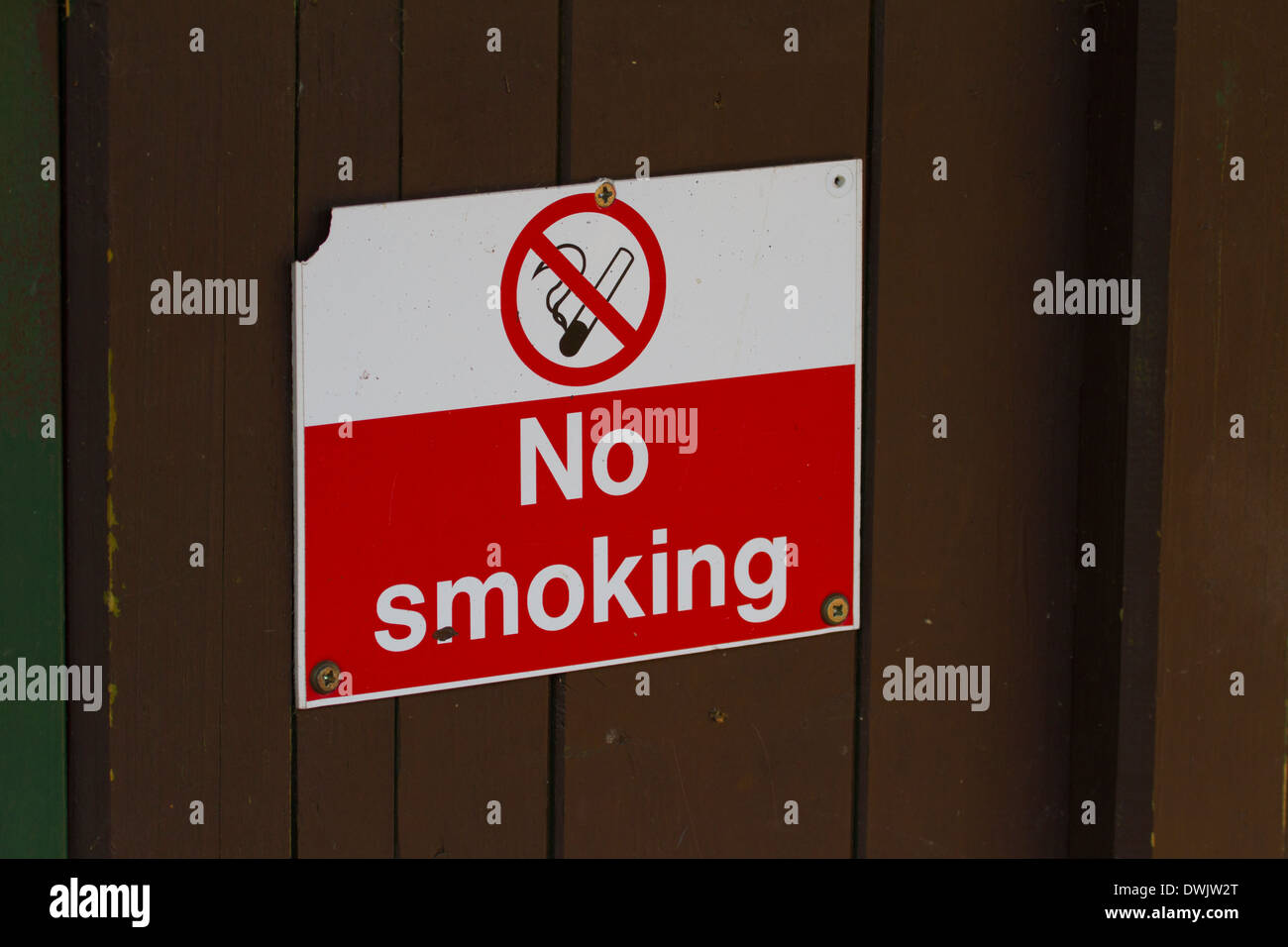 dirty broken no smoking sign screwed to wooden fence gate - Stock Image