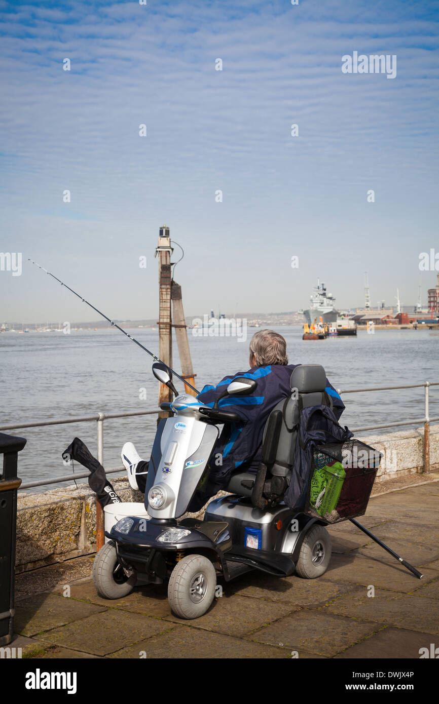 Man fishing at Portsmouth Harbour from Powered disability scooter. - Stock Image