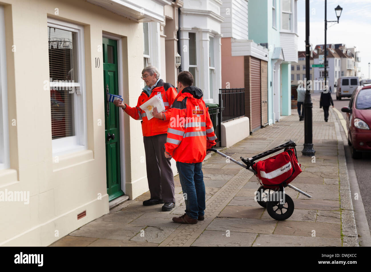 Two postmen with two wheeled postal trolley delivering post on city street. Stock Photo
