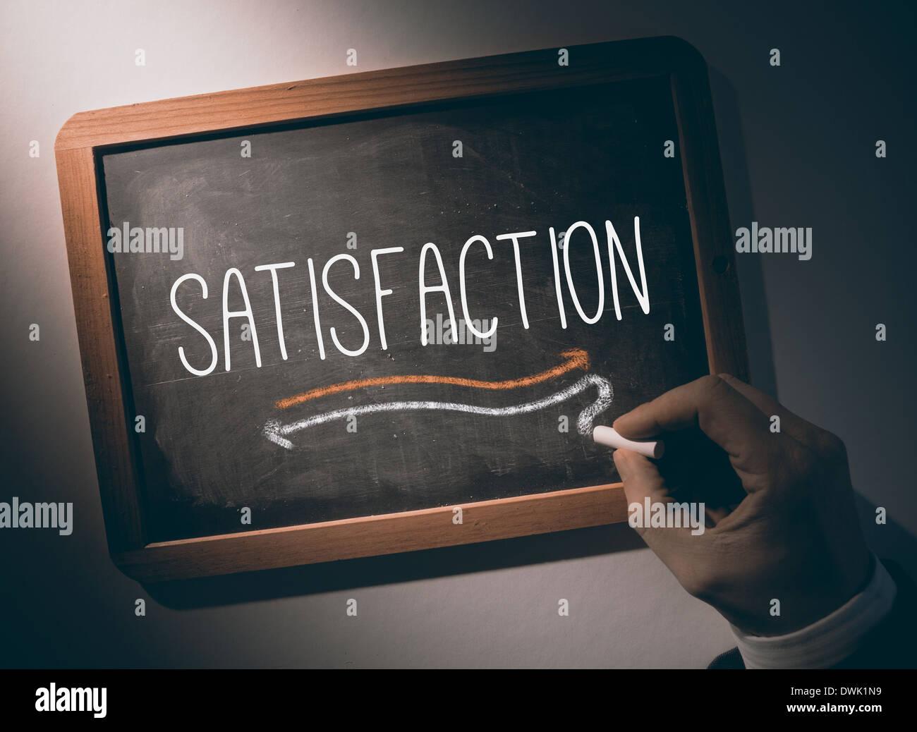 Hand writing Satisfaction on chalkboard - Stock Image