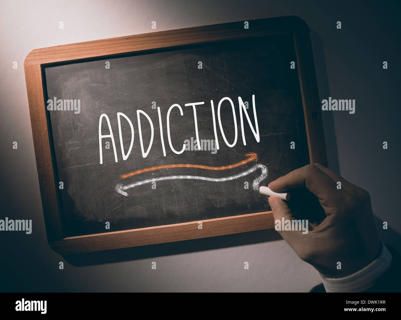 Hand writing Addiction on chalkboard - Stock Image
