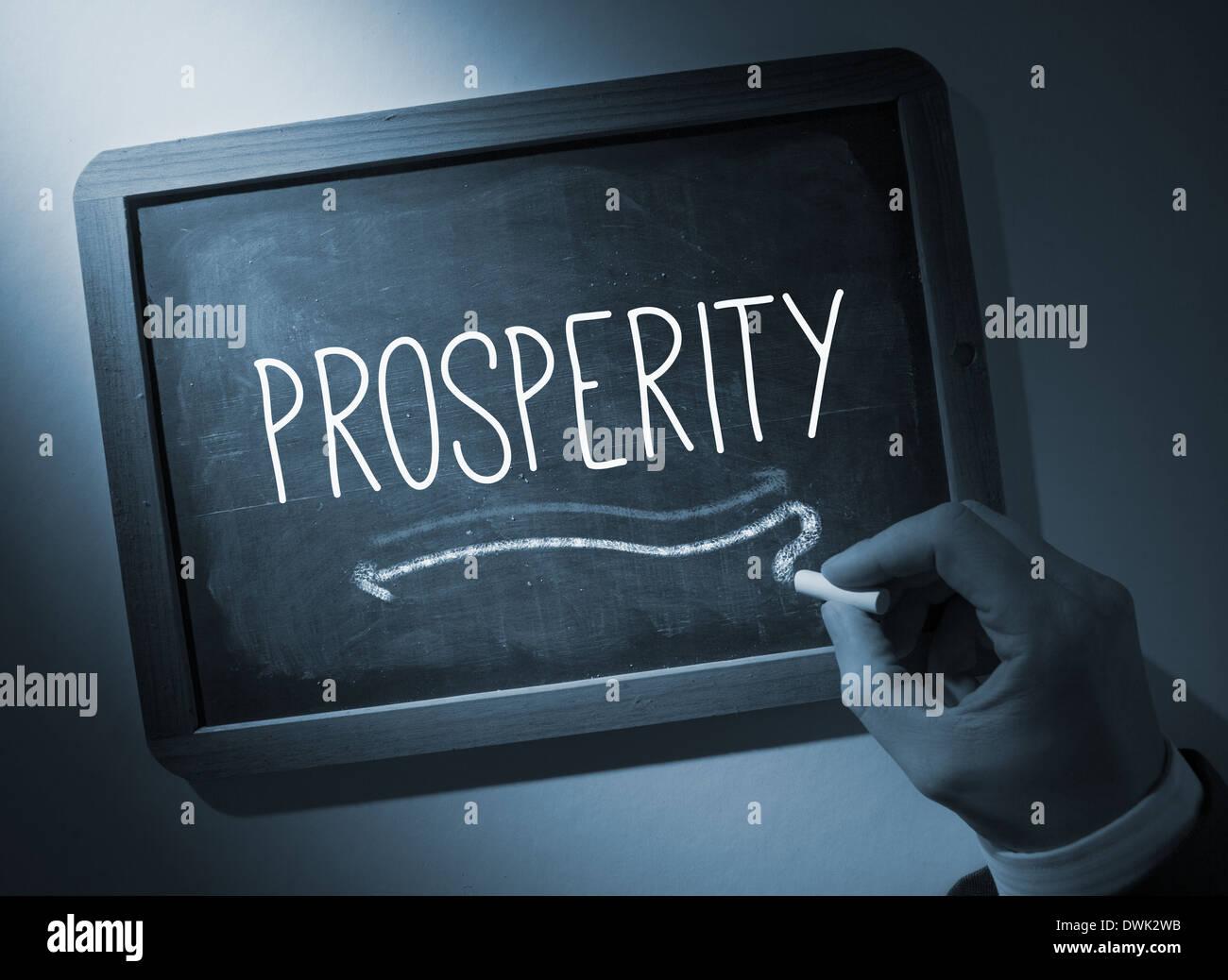 Hand writing Prosperity on chalkboard - Stock Image