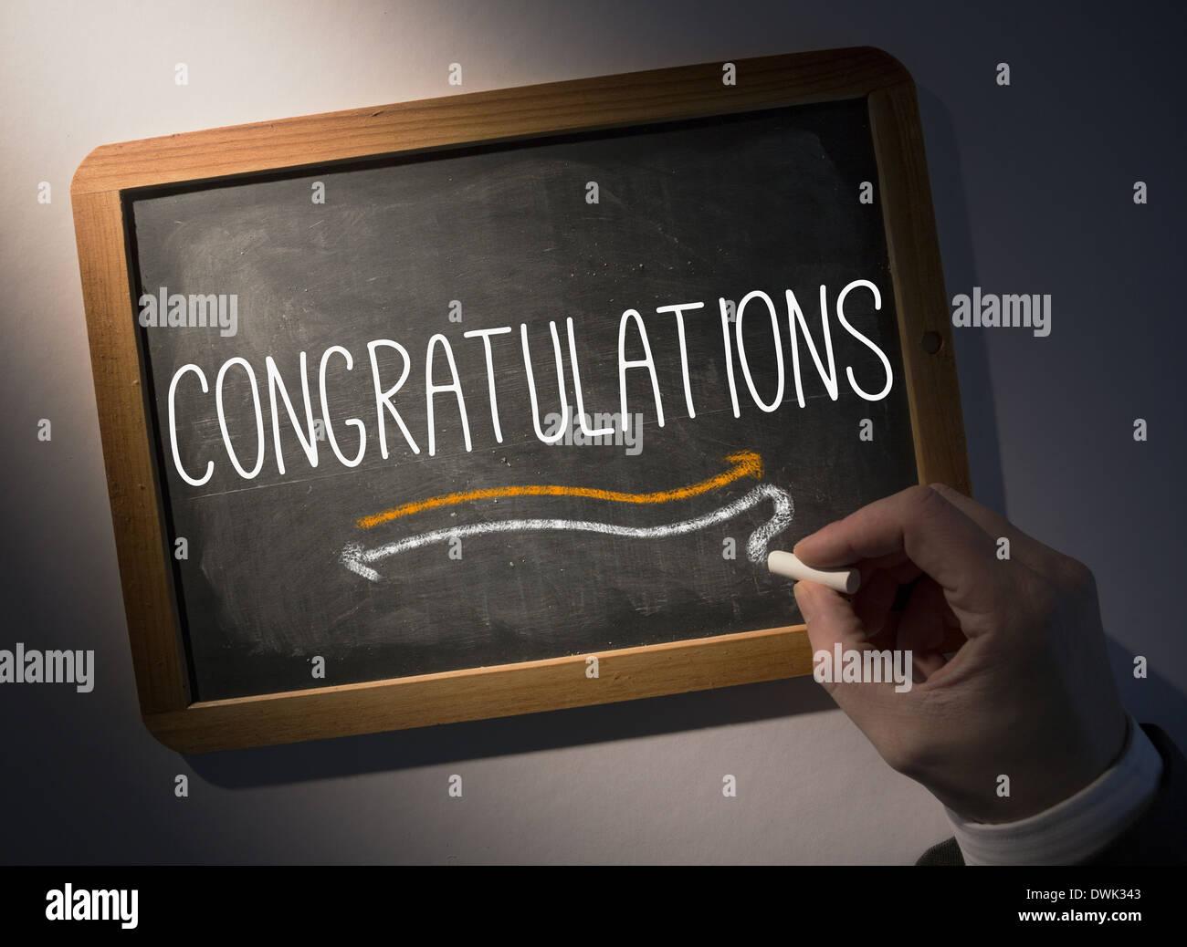 Hand writing Congratulations on chalkboard - Stock Image
