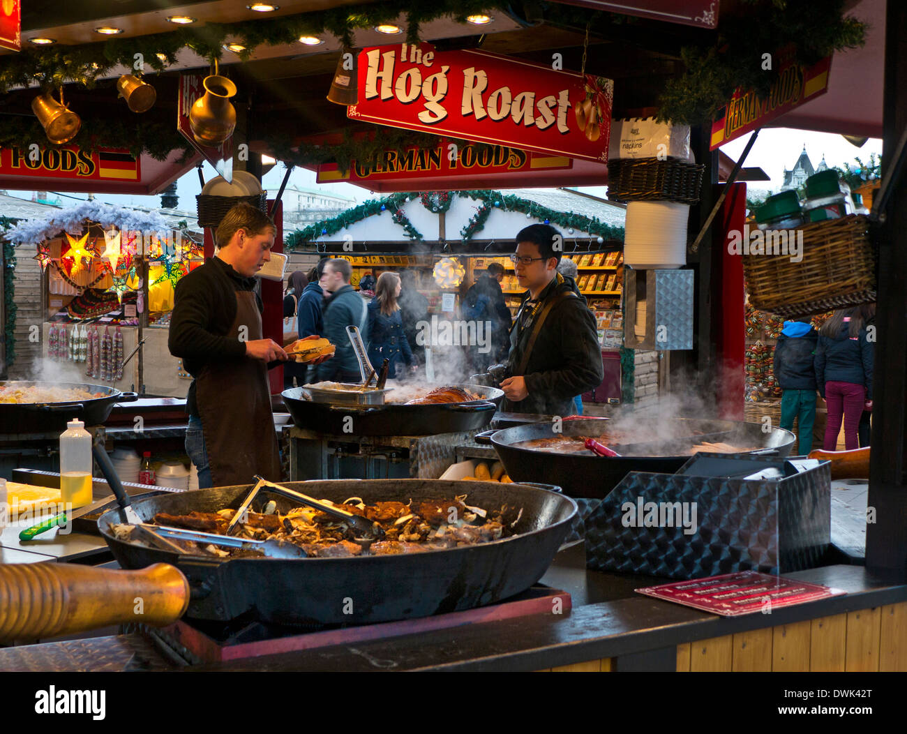 SouthBank German Christmas market takeaway hog roast food stall and visitors London UK - Stock Image