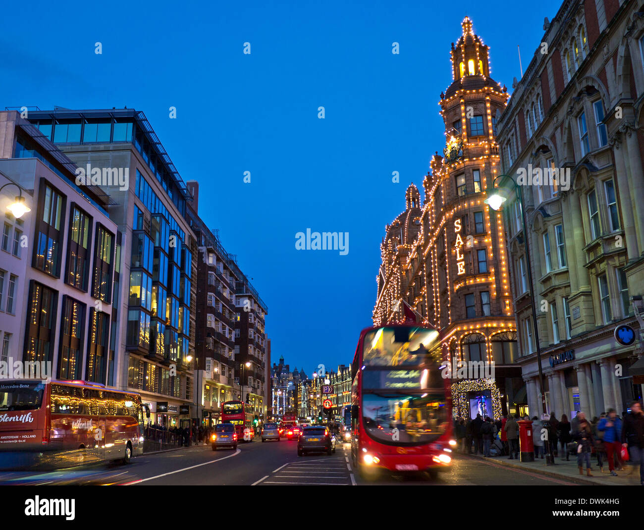 Brompton Road and Harrods department store at dusk with lit 'Sale' sign shoppers red buses and taxis Knightsbridge London SW1 - Stock Image
