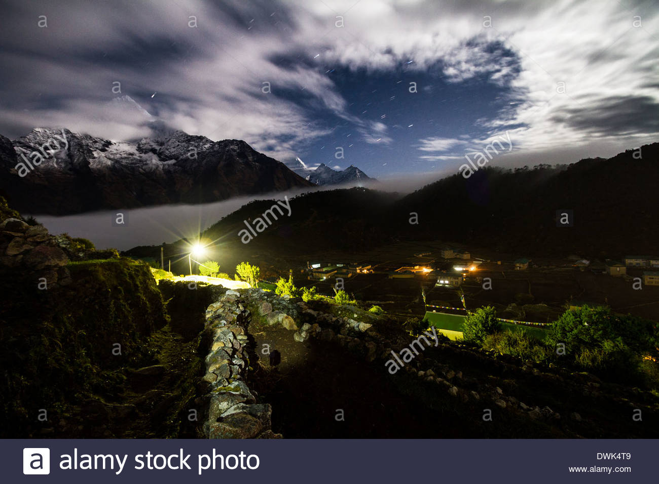 The Sherpa village of Khumjung is seen in the foreground as wind swept clouds race over the Himalayas peaks in the background. - Stock Image