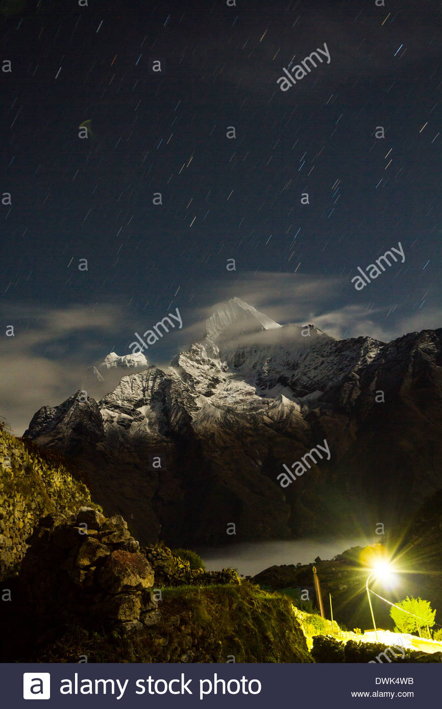 Thamserku and Kangtega are seen under a sky full of stars from the Sherpa village of Khumjung, Nepal - Stock Image