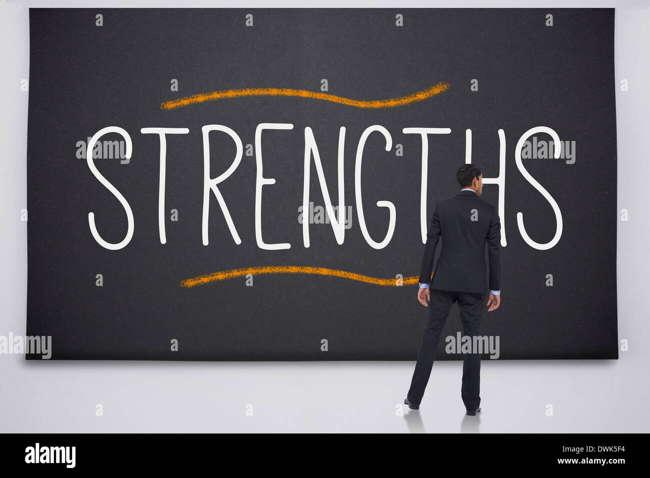 Businessman reading the word strengths - Stock Image
