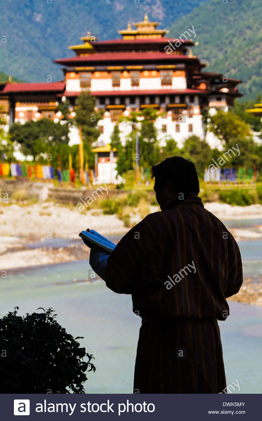 The Punakha Dzong is seen across the Mo Chhu River in central Bhutan while Buddhist prayer flags flutter nearby - Stock Image