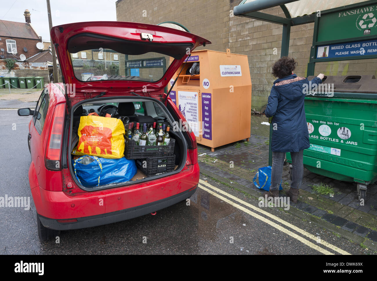 Women with a car boot full of bottles at a recycling bottle bank - Stock Image