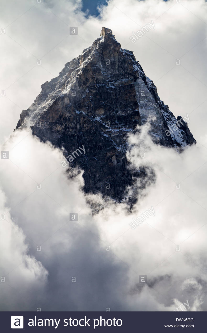 A solemn black Himalayan peak rises above swirling clouds below in Nepal - Stock Image