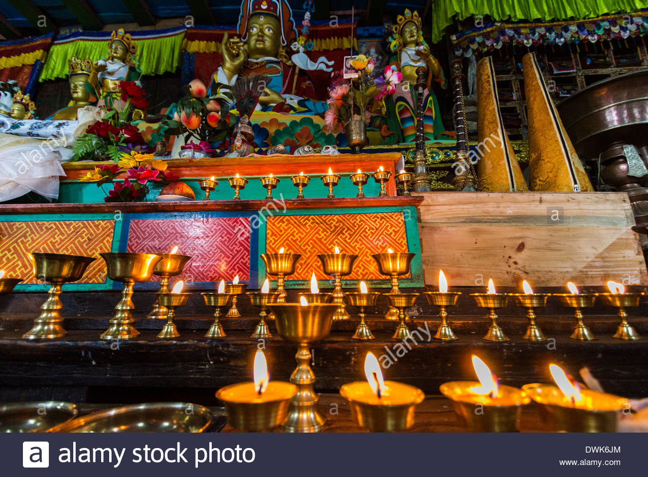 Butter candles sit in front of a statue of Guru Rinpoche in teh Khumjung Monastery in Khumjung, Nepal - Stock Image