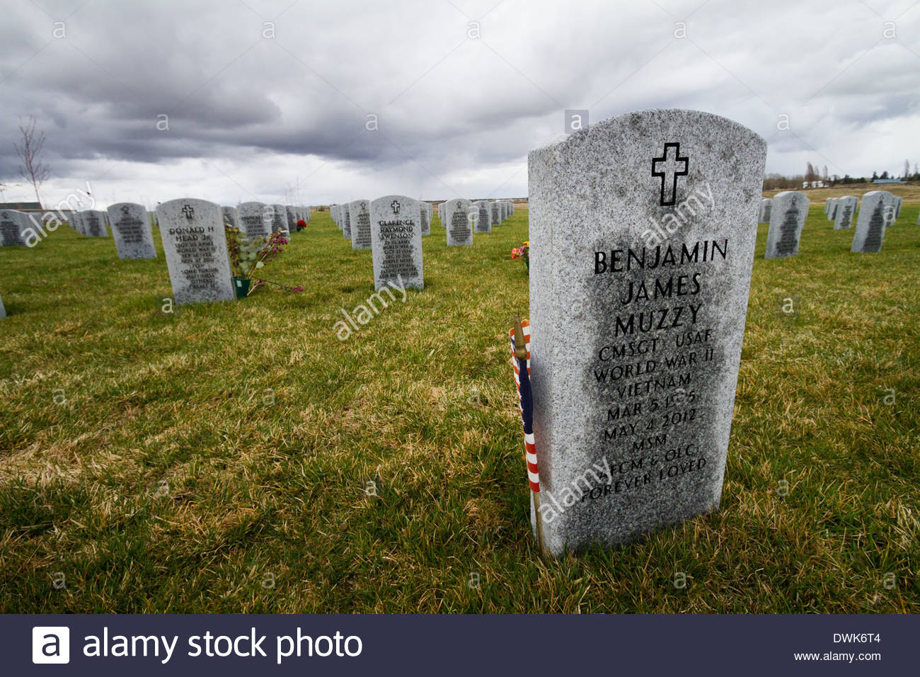 Miltary grave tombstones with American flags sit under a gray sky in Eastern Washington state, USA - Stock Image