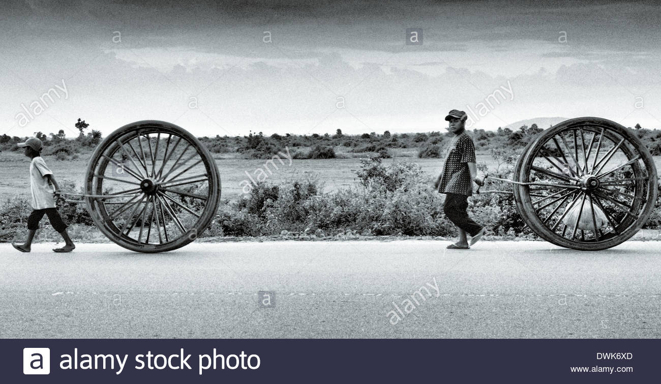 A Khmer father and son rolling cart wheels into the local town Siem Reap, Cambodia, South East Asia. - Stock Image
