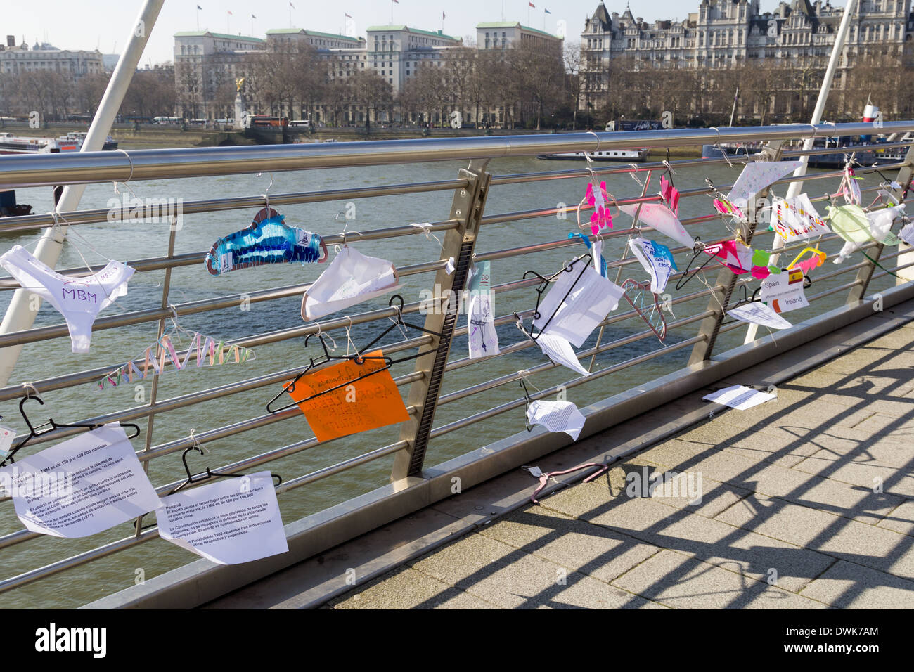 LONDON, UK - 9TH MARCH 2014: Coat Hangers with writing on hanging on Hungerford Bridge in London - Stock Image