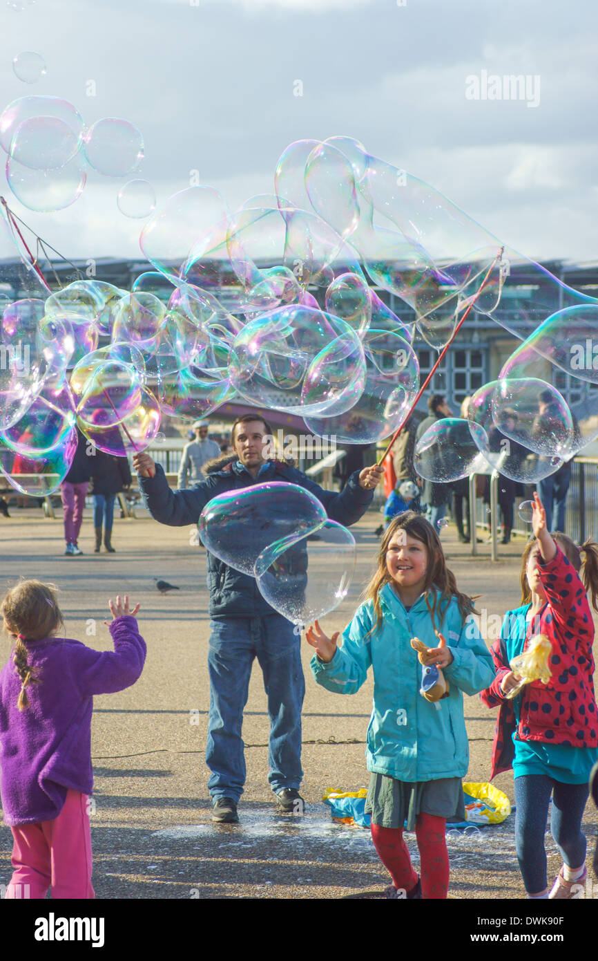 Street entertainer blows bubbles for children  London South bank.  Children playing with bubbles - Stock Image
