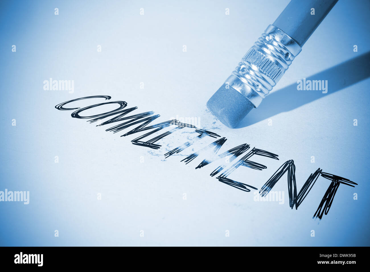 Pencil erasing the word Commitment - Stock Image
