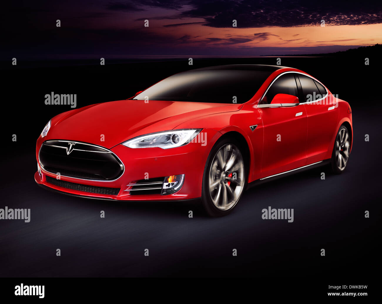 Red 2014 Tesla Model S luxury electric car outdoors on tthe road at night - Stock Image