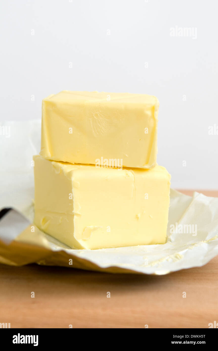 Open pack of butter on wooden chopping board - Stock Image