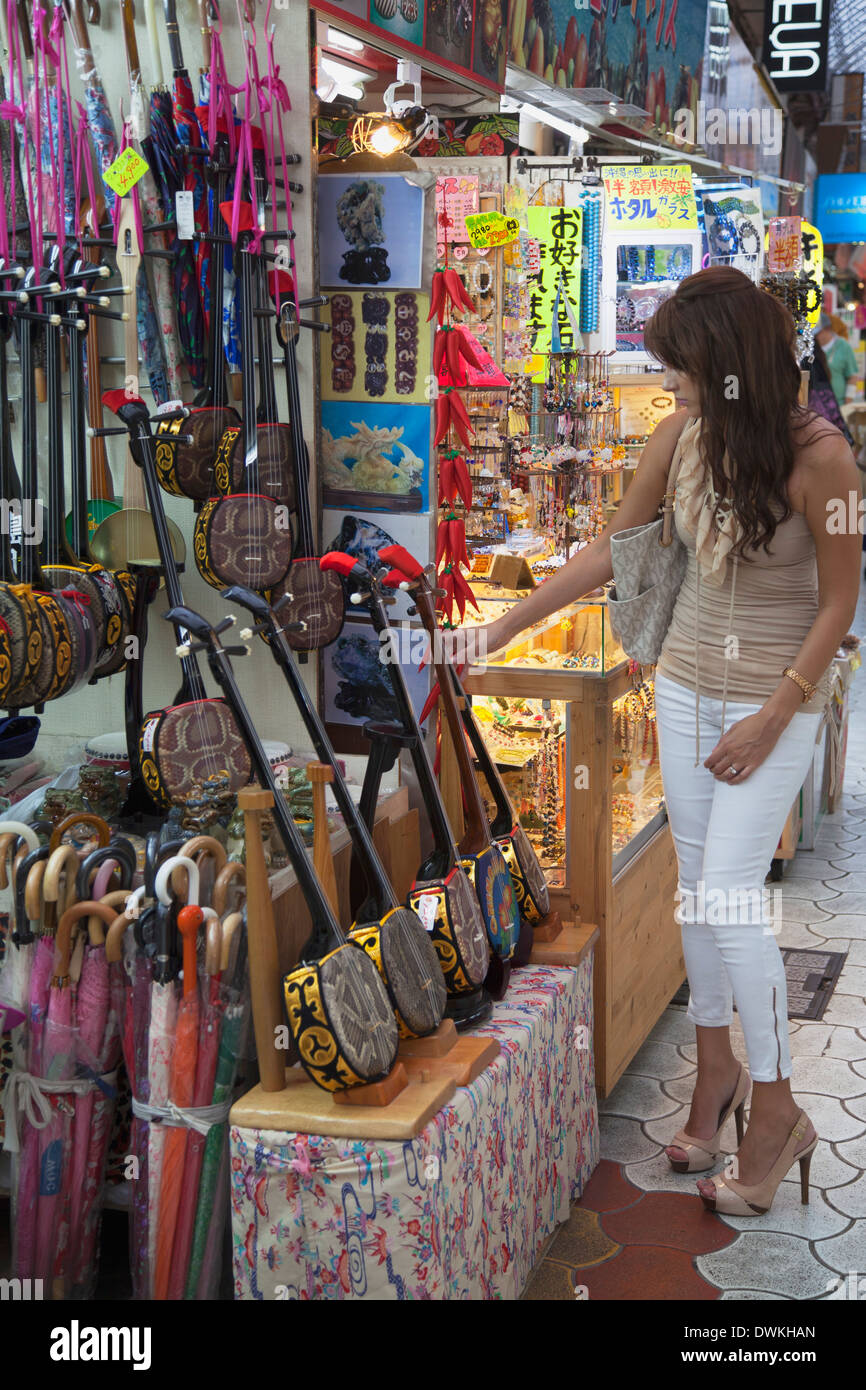 Woman looking at sanshin, an Okinawan musical instrument, in Ichibahon-dori indoor shopping arcade, Naha, Okinawa, Japan, Asia - Stock Image