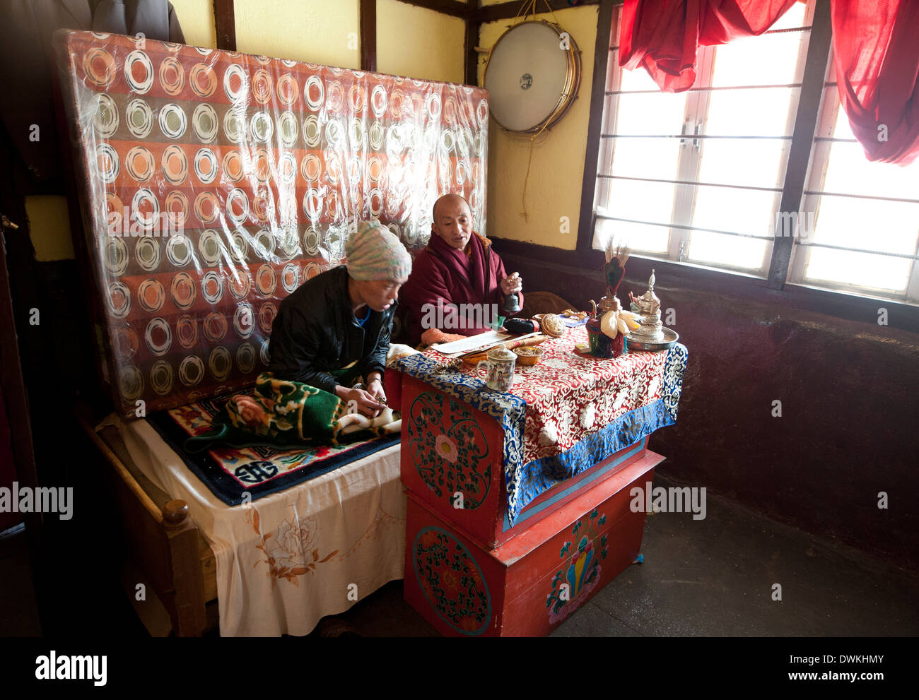 Two Buddhist men chanting a Buddhist mantra inside roadside tea stall at the Sela Pass, Arunachal Pradesh, India - Stock Image