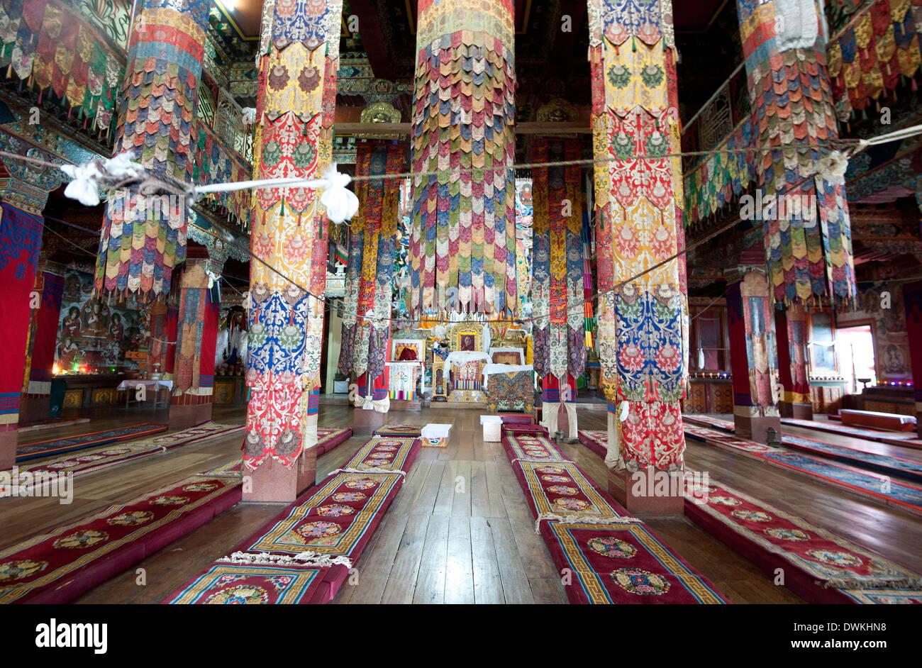 Prayer hall in Tawang Buddhist monastery with pillars covered in prayer flags, Tawang, Arunachal Pradesh, India - Stock Image