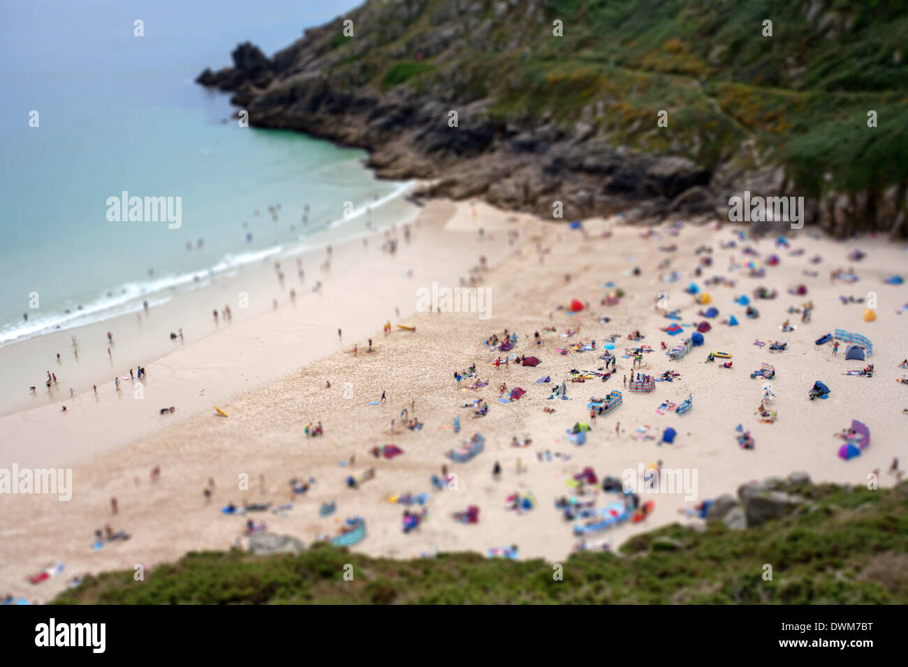 Holiday makers on the beach Porthcurno, Cornwall, UK Tilt shift effect - Stock Image
