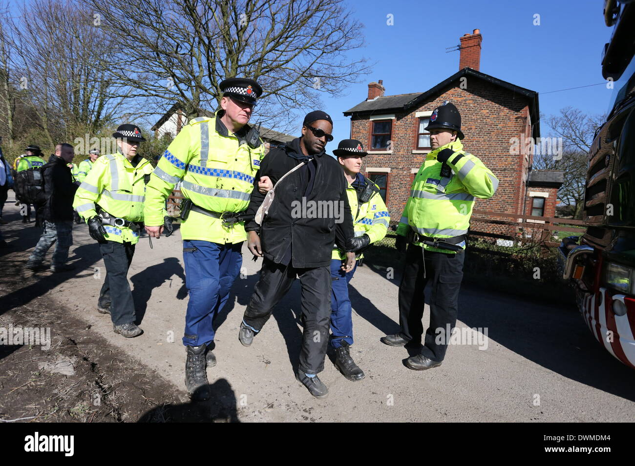 Salford, UK. 11th Mar, 2014. A protester is arrested as lorries arrive. Anti-fracking protesters have been granted a stay of execution by the court of appeal. Anti-fracking protesters were ordered to leave the Barton Moss protest camp after landowners Peel Holdings asked Manchester Civil Justice Centre for possession of the camp. The court order said that protesters must leave the site before 12 noon on Tuesday, 11th March, 2014. Credit:  Christopher Middleton/Alamy Live News - Stock Image