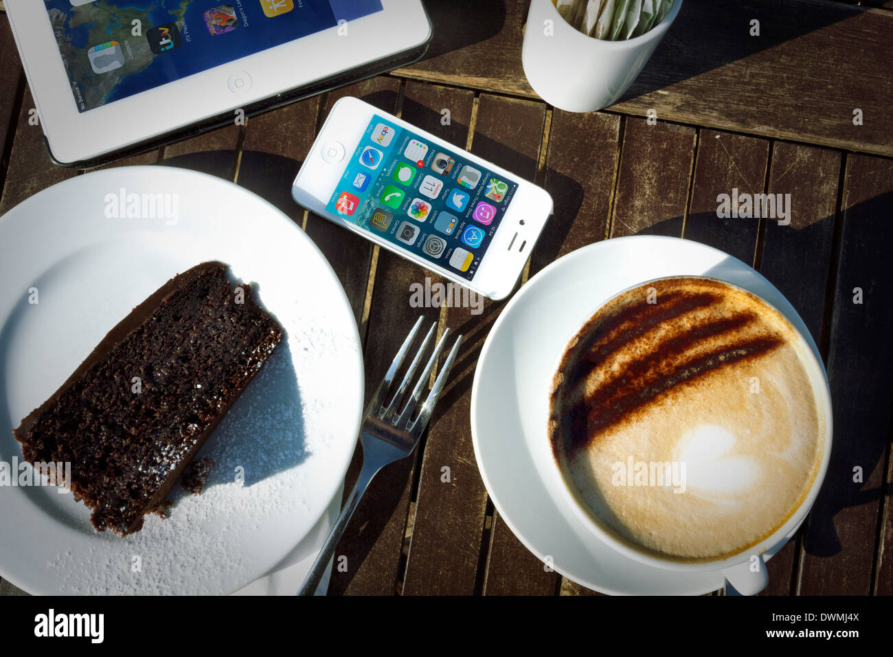 iPhone 4s, iPad 2 And Cake And Cappuccino On Table In Sunlight - Stock Image