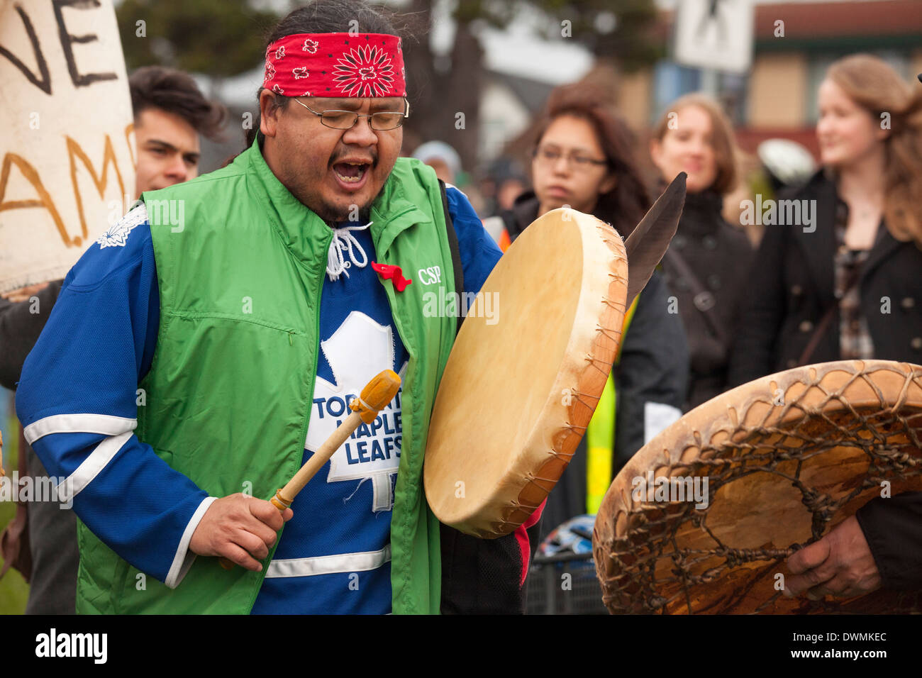 Aboriginal First nations man beating drum with demonstrators at Anti oil pipeline rally-Victoria, British Columbia, Canada. - Stock Image