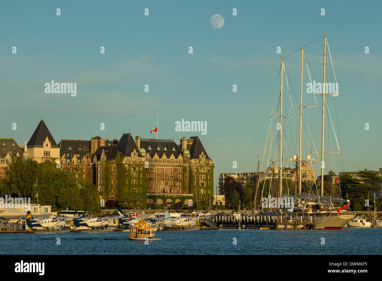 Nearly Full moon rising behind Empress hotel and Inner harbor-Victoria, British Columbia, Canada. Stock Photo