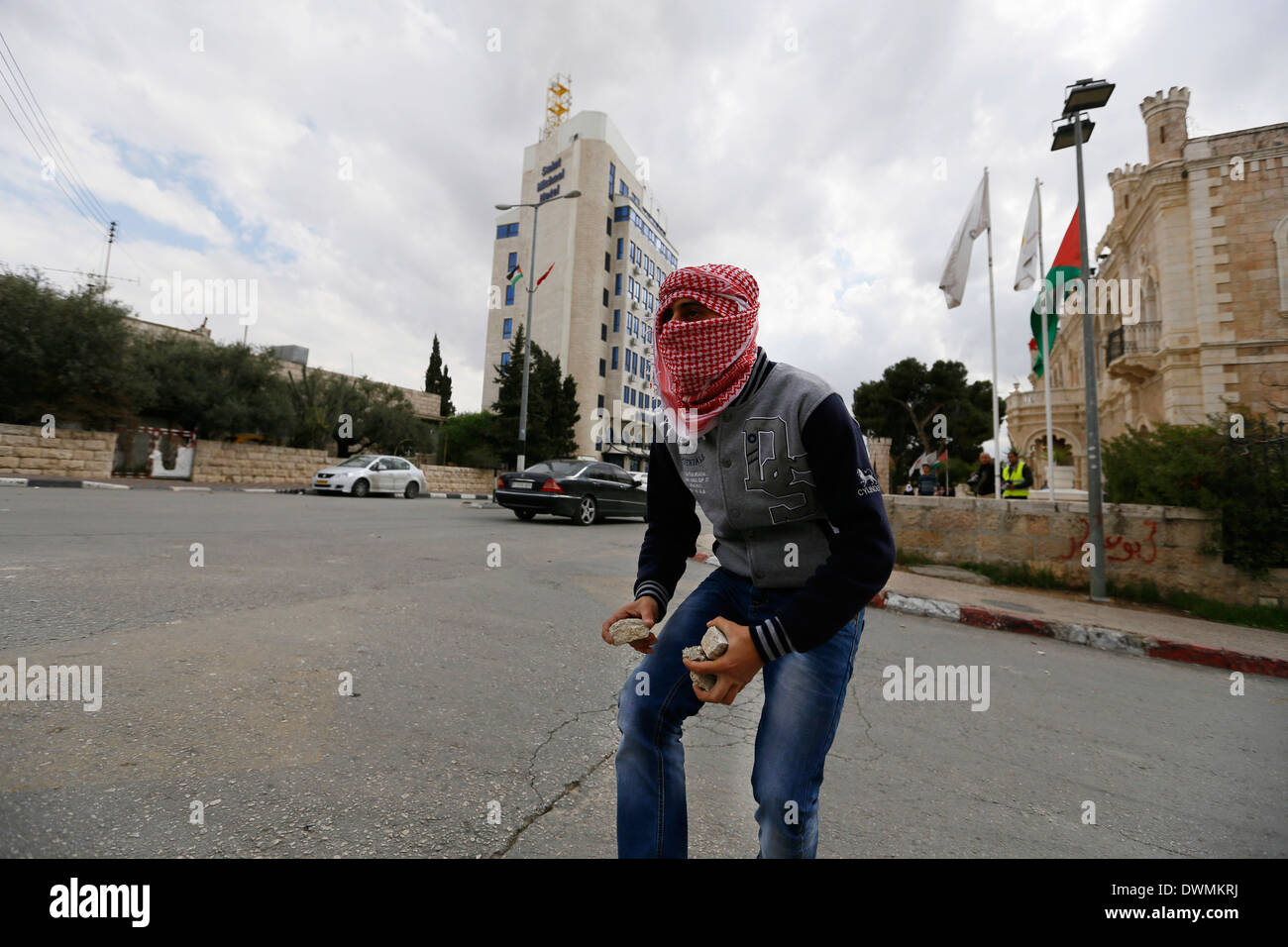 Masked Palestinian throwing stones at the Israeli soldiers, during clashes. - Stock Image